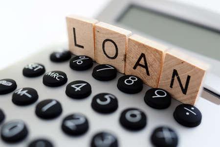 Rekenmachine met het woord lening geschreven in houten blokletters Stockfoto