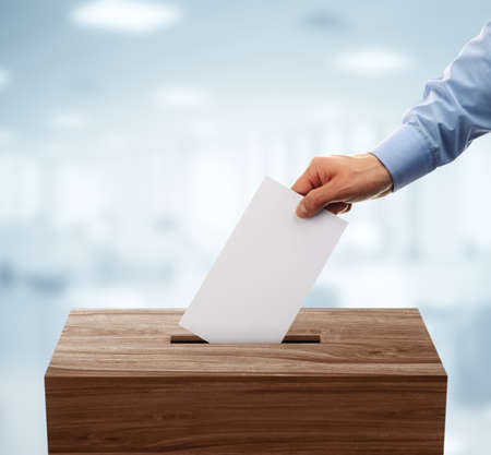 elections: Ballot box with person casting vote on blank voting slip