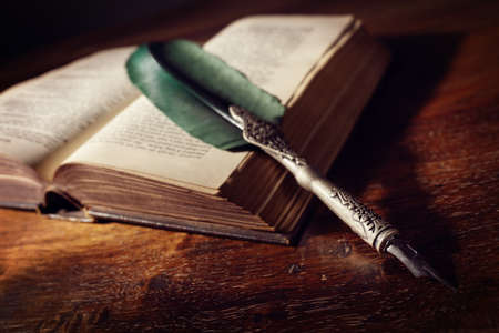 manuscript: Quill pen resting on an old book on a desk concept for literature, writing, author and history