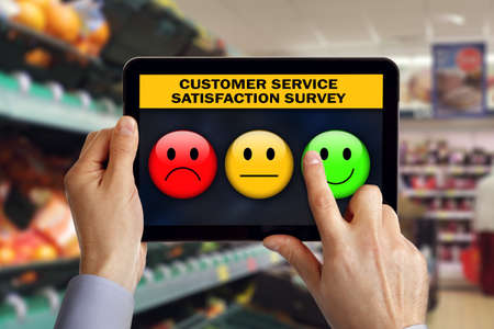 Digital-Tablette im Shop mit Kundenrezensionen ein Servicezufriedenheit Umfrage der Auswahl eines glücklich smiley Emoticon Standard-Bild