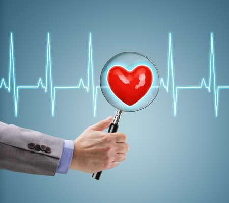 Herz-Gesundheitscheck, Doktor mit Vergrößerungsglas auf einem Herz und EKG-Diagramm