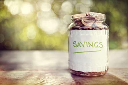 fondos negocios: Tarro de dinero Ahorros lleno de monedas de concepto para el ahorro o la inversión para una casa, jubilación o la educación Foto de archivo