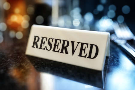 Restaurant reserved table sign with places setting and wine glasses ready for a party Archivio Fotografico