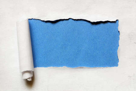 Torn paper over a blank blue background for message Stockfoto