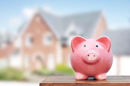 Enregistrement d'acheter une maison, de l'immobilier ou d'épargne logement, la tirelire en face de la propriété Banque d'images - 48355401