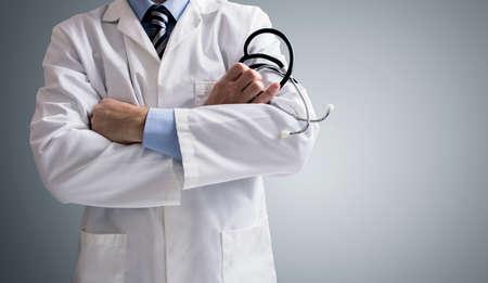recetas medicas: Doctor que sostiene un estetoscopio con los brazos cruzados y el espacio de la copia Foto de archivo