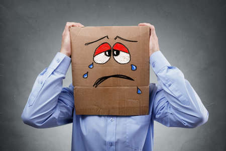 headache pain: Businessman with cardboard box on his head showing a crying sad expression concept for headache, depression, sadness, heartache or frustration