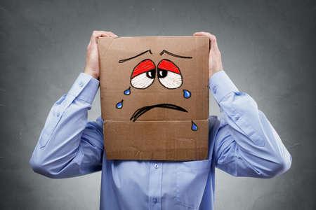 Geschäftsmann mit Kartons auf dem Kopf, die eine weint traurigen Ausdruck Konzept für Kopfschmerzen, Depression, Traurigkeit, Kummer und Frustration