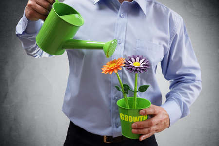 making money: Investment and growth businessman with watering can investing in business and making money concept Stock Photo