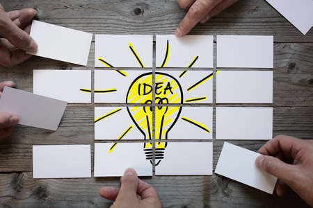 breaking new ground: Business team brainstorming and finding a solution or good idea with light bulb drawing on business card paper
