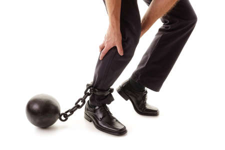 prison ball: Ball and chain restraining a businessman as he tries to walk concept for business burden, willpower and determination