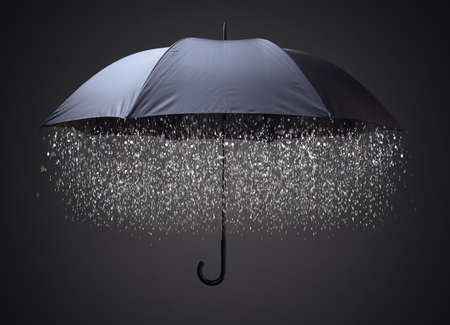 april showers: Rain drops falling from inside a black umbrella concept for business and financial problems, challenge or insurance protection Stock Photo