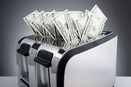 Money to burn concept, one hundred dollar bills burning in a toaster
