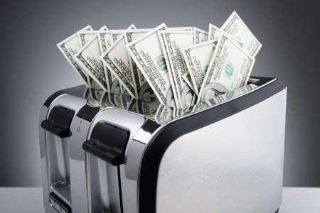 Geld-Konzept, hundert Dollar-Scheine in einem Toaster brennen zu verbrennen