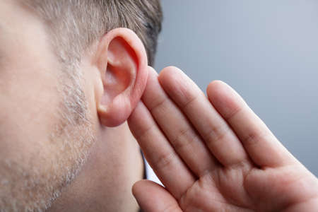 oir: El hombre con la mano en el oído escucha de sonido bajo o prestar atención