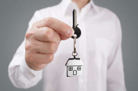 llaves: Man holding out house key on a house shaped keychain