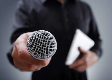 spokesperson: Hand holding a microphone conducting a business interview or press conference