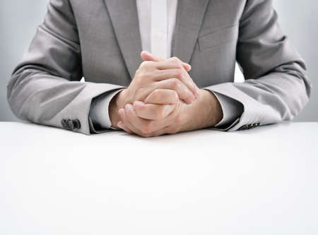 work table: Businessman at desk in business job interview with hands clasped, attentive and listening in anticipation