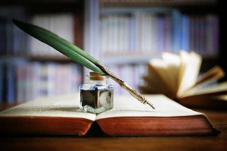 Plume et encre bien reposant sur un vieux livre dans un concept de bibliothèque pour la littérature, l'écriture, l'auteur et l'histoire