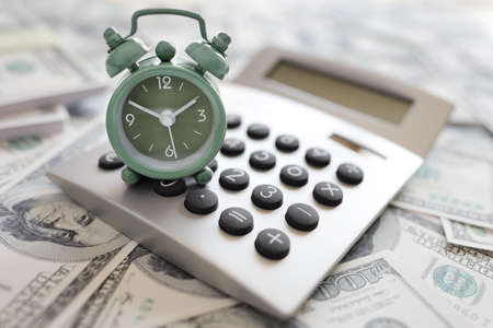 cost: Calculator and alarm clock on money concept for time is money or tax and savings deadline Stock Photo
