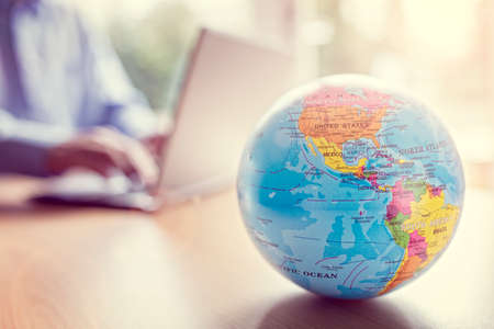 Zakenman met behulp van een laptop met close-up op wereldbol Stockfoto