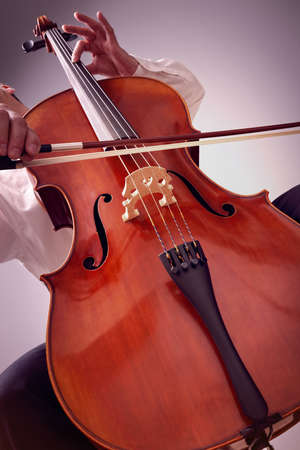 cellist: Cello player or cellist performing in an orchestra concept for music lessons, education and the arts Stock Photo