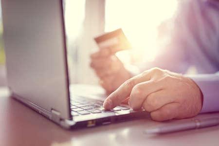 Man met een creditcard met behulp van een laptop computer voor internet winkelen