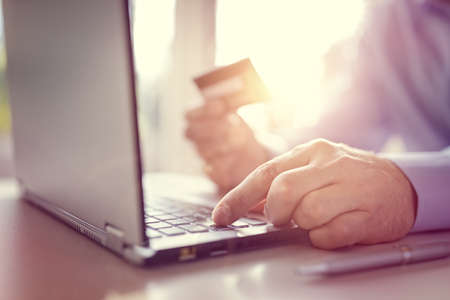 debit: Man with credit card using a laptop computer for internet shopping Stock Photo