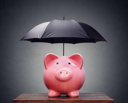 Spaarvarken met paraplu concept voor financiën verzekeringen, bescherming, veilige investering of banking Stockfoto