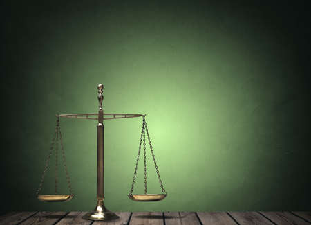 litigate: Law scales on wooden desk concept for justice and equality