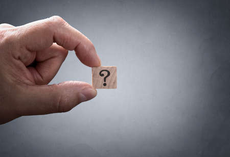 thumbs: Businessman holding a question mark concept for confusion, question or solution