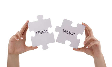 holding aloft: Puzzle pieces joining together to read  teamwork concept for unity, business team or partnership Stock Photo