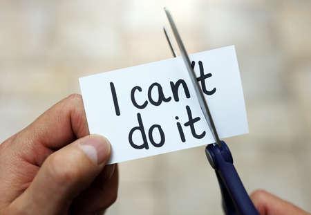 actitud positiva: El hombre usando tijeras para quitar la palabra no puede leer que puede hacerlo concepto de fe en s� misma, la actitud positiva y la motivaci�n Foto de archivo