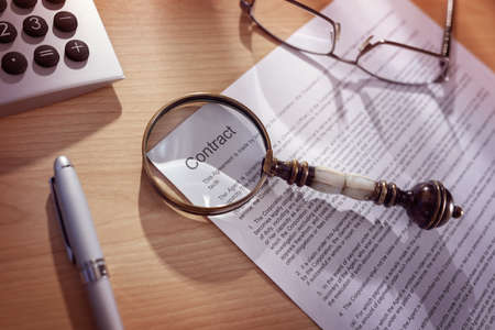 fine print: Magnifying glass examining and signing a legal contract document