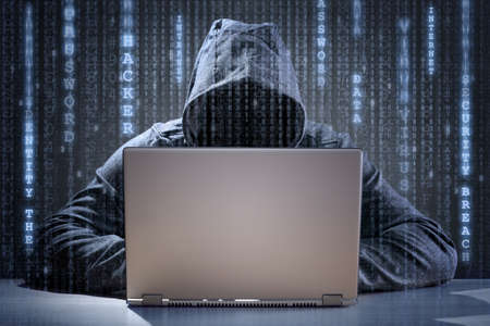 Computer hacker stealing data from a laptop concept for network security, identity theft and computer crime