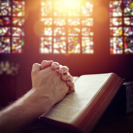 Hands folded in prayer on a Holy Bible in church concept for faith, spirtuality and religion Stockfoto
