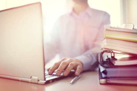libros: El hombre de negocios o un dise�ador que usa el ordenador port�til en el escritorio en la oficina Foto de archivo