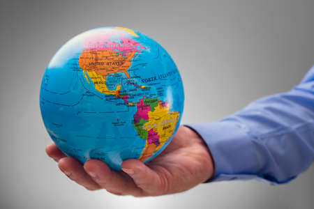 businessman carrying a globe: Businessman holding the world in the palm of his hands concept for global business, communications, politics, geography or environmental conservation