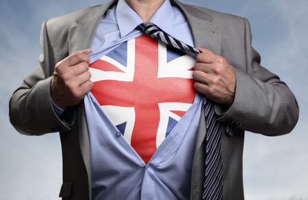 national hero: Businessman in classic superman pose tearing his shirt open to reveal t shirt with the British union jack flag concept for european referendum, patriotism, freedom and national pride