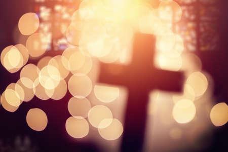 Streszczenie defocussed krzyż sylwetka w kościelnym wnętrzu przeciw barwionego szkła okno koncepcji religii i modlitwy