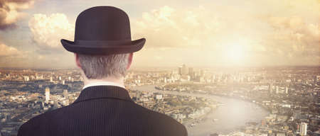 successful man: Businessman with bowler hat looking at financial city skyline concept for finance, investment, career and opportunity Stock Photo