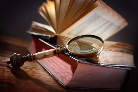 Book and magnifying glass concept for education, knowledge and searching for information