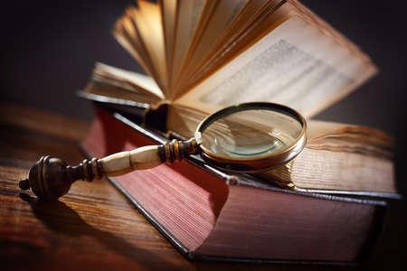 libros abiertos: Libro y lupa concepto de vidrio para la educación, el conocimiento y la búsqueda de información Foto de archivo