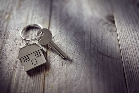 key: House key on a house shaped keychain resting on wooden floorboards concept for real estate, moving home or renting property