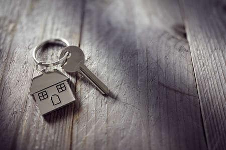 Klucz Dom na pęku kluczy w kształcie domu spoczywającej na drewnianej deski podłogowe koncepcja nieruchomości, przeniesienie domu lub wynajmę