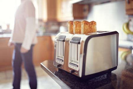 pain: T�t le matin, pain grill�, l'homme dans la cuisine pour pr�parer des toasts pour le petit d�jeuner au lever du soleil Banque d'images