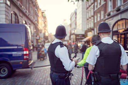 policing: British police officers in helmets policing London streets