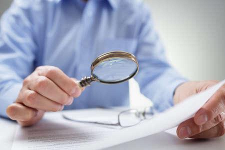 Geschäftsmannlesedokumente mit Lupe Konzept zur Analyse einer Finanzierungsvereinbarung oder Rechtsvertrag