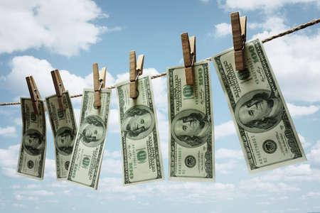dollaro: Cento fatture del dollaro che pendono da un concetto di clothesline per il riciclaggio di denaro, di investimento o fondi di capitale di rischio