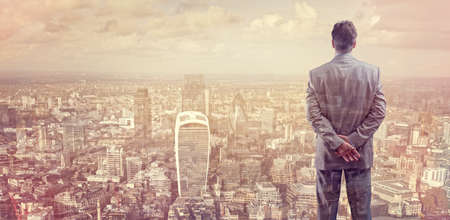Businessman looking across the city of London financial district concept for entrepreneur, leadership and success Фото со стока